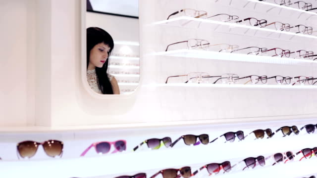 woman is choosing a pair of glasses in optic shop - visual merchandising stock videos and b-roll footage