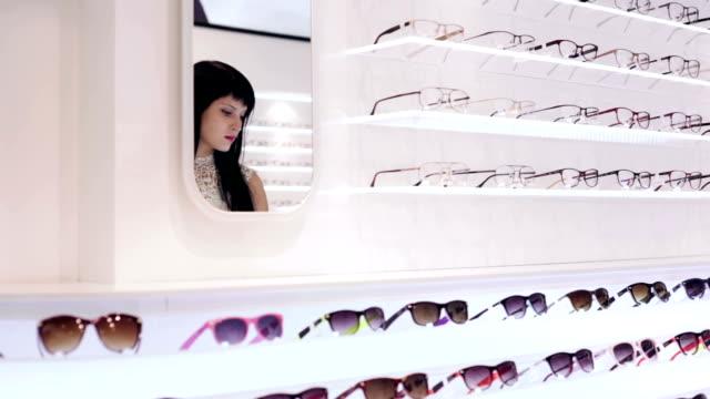 frau ist sie ein paar gläser in blinder shop - sehvermögen stock-videos und b-roll-filmmaterial