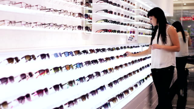 woman is choosing a pair of sunglasses in optic shop - visual merchandising stock videos and b-roll footage
