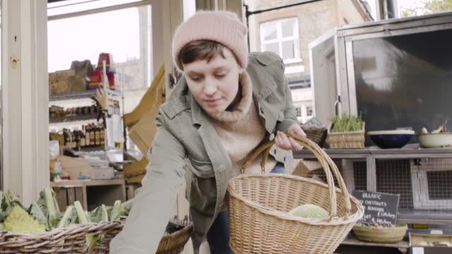 Woman is choosing organic tomatoes at organic farm market.
