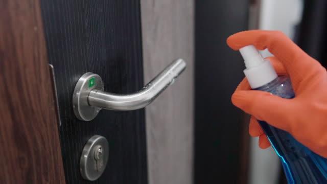 女性は消毒製品でドアノブを掃除し、保護手袋を着用しています。 - 片付いた部屋点の映像素材/bロール