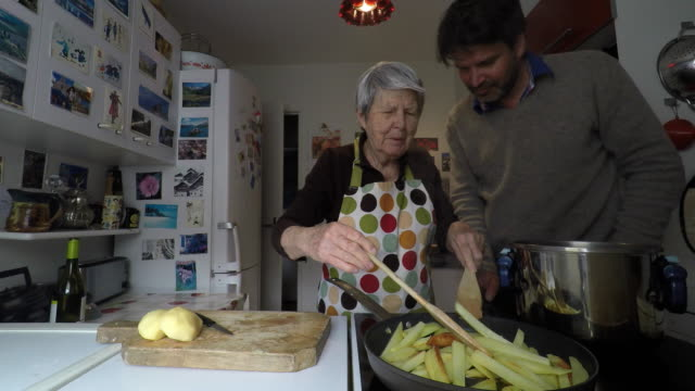 woman is cooking with her son