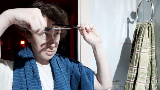 vídeos de stock, filmes e b-roll de a mulher está cortando o cabelo. - domestic bathroom