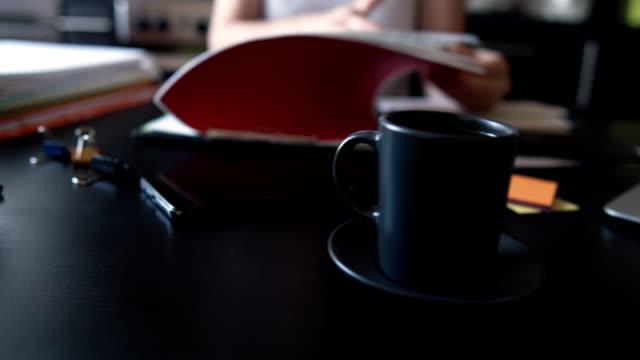 女性は国内のキッチンで彼女のオフィスの仕事をしています - ホッチキス点の映像素材/bロール