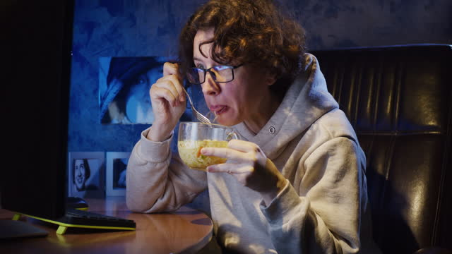 woman is eating instant noodles while watching video at the computer in the dark room - noodles stock videos & royalty-free footage