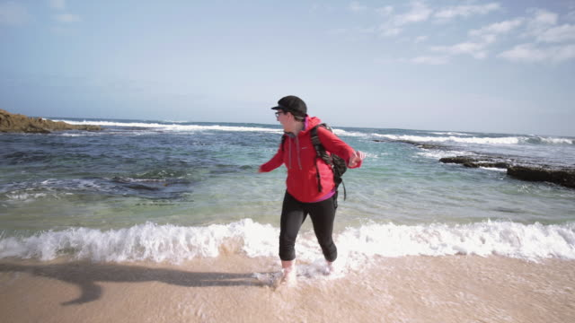 A woman is escaping from the waves, at Mornington Peninsula, Victoria, Australia
