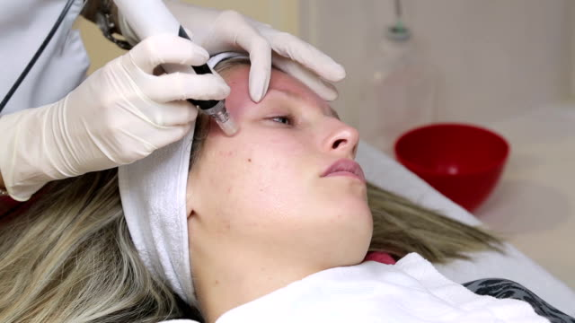 Woman is getting a mesotherapy of her face