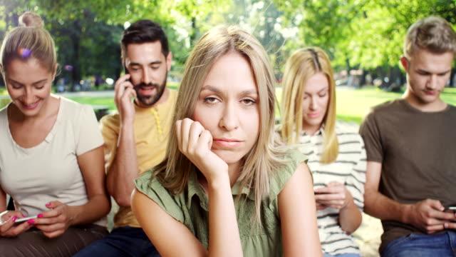 kvinnan är att bli uttråkad medan alla hans vänner tittar på telefon - missbrukare av droger bildbanksvideor och videomaterial från bakom kulisserna