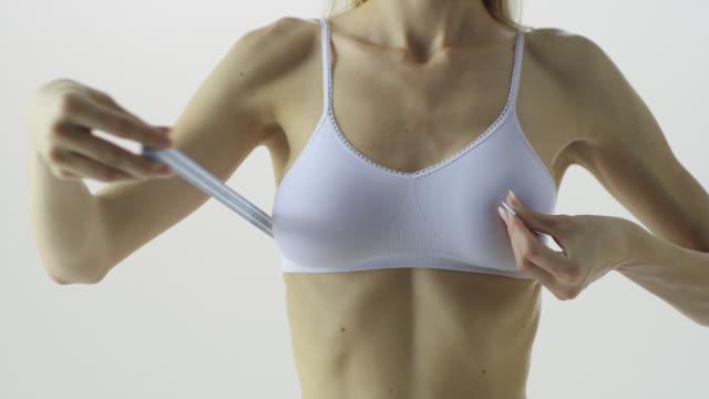 vídeos de stock e filmes b-roll de woman is girthing her breast with tapemeasure. close-up. - medir