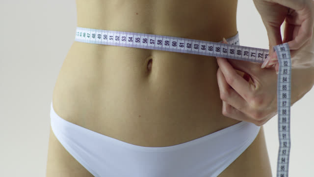 woman is girthing her waist with tapemeasure. close-up. - tape measure stock videos & royalty-free footage