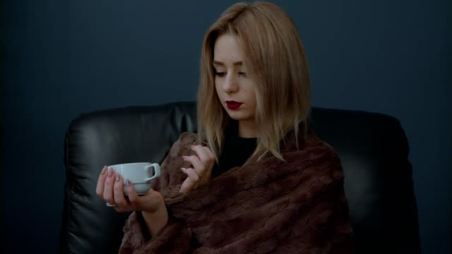 Woman is going to drink hot coffee and wrapped in a blanket from the cold