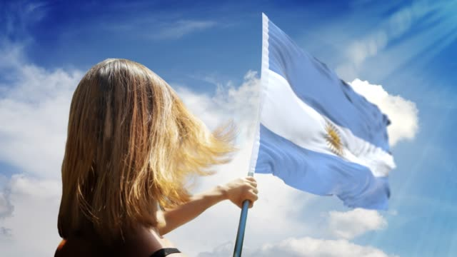 frau hält flagge pole mit argentinischer flagge beim tragen maske gegen coronavirus covid-19 in 4k-auflösung - argentinische flagge stock-videos und b-roll-filmmaterial