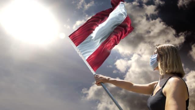 frau hält flagge pole mit österreichischer flagge beim tragen von maske gegen coronavirus covid-19 in 4k-auflösung - flag stock-videos und b-roll-filmmaterial