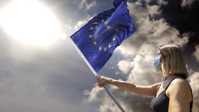 woman is holding flag pole with european union flag while wearing mask against coronavirus covid-19 in 4k resolution - eu flag stock videos & royalty-free footage