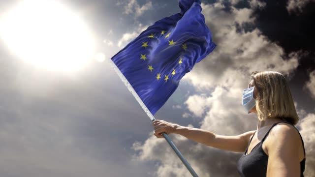 女性は4k解像度でコロナウイルスcovid-19に対してマスクを着用しながら、欧州連合(eu)フラグで旗のポールを保持しています - 欧州連合旗点の映像素材/bロール