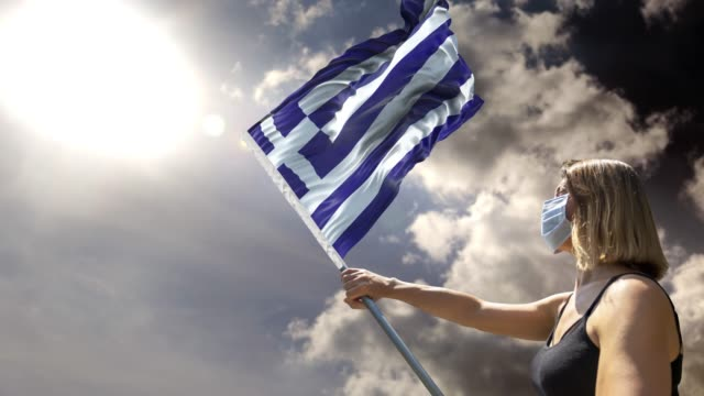 woman is holding flag pole with greek flag while wearing mask against coronavirus covid-19 in 4k resolution - greek flag stock videos & royalty-free footage