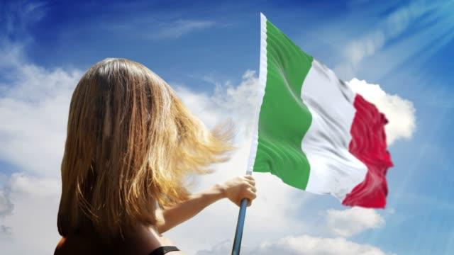 女性は4k解像度でイタリアの旗と旗のポールを保持しています - イタリア国旗点の映像素材/bロール