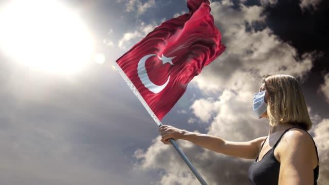 vidéos et rushes de la femme tient le poteau de drapeau avec le drapeau turc tout en portant le masque contre le coronavirus covid-19 dans la résolution 4k - drapeau turc