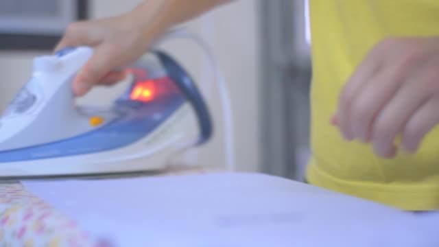 女性は家で衣類にアイロンをかけています。 - アイロン点の映像素材/bロール