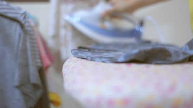 女性は家で服にアイロンをかけている。 - アイロン台点の映像素材/bロール