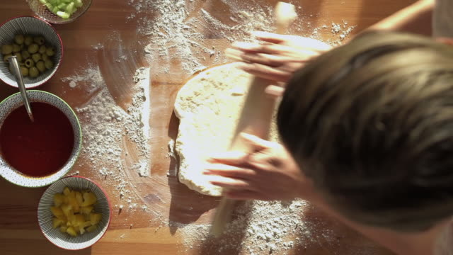 woman is kneading a pizza dough with a rolling pin, high angle view - table top view stock-videos und b-roll-filmmaterial