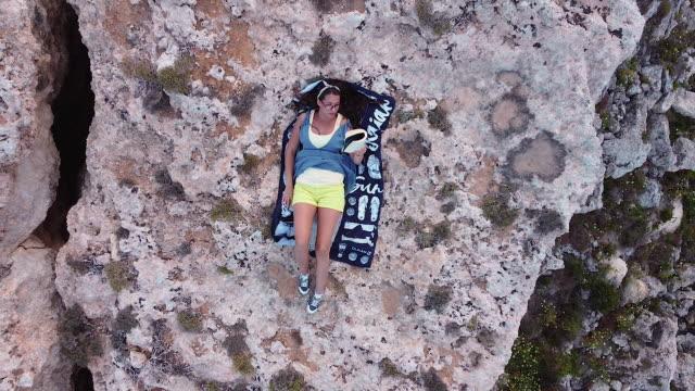 vídeos de stock, filmes e b-roll de mulher está deitada, relaxando e lendo um livro lá fora - falésia