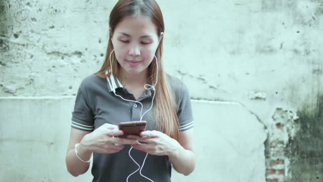woman is listening music by her smartphone - taiwan stock videos and b-roll footage