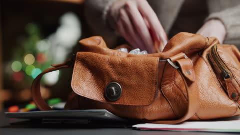 vídeos y material grabado en eventos de stock de mujer está buscando algo en su bolso en el escritorio en la víspera de navidad - en búsqueda