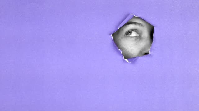 woman is looking through colorful torn paper - peeking stock videos & royalty-free footage