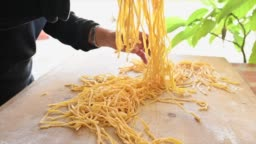 A woman is making fresh pasta called 'Fettuccine' made from fresh eggs and durum wheat flour. Fettuccine is a flat thick pasta popular in Roman and Tuscan cuisine.