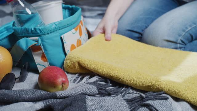 woman is placing towel on beach blanket - tartan stock videos & royalty-free footage