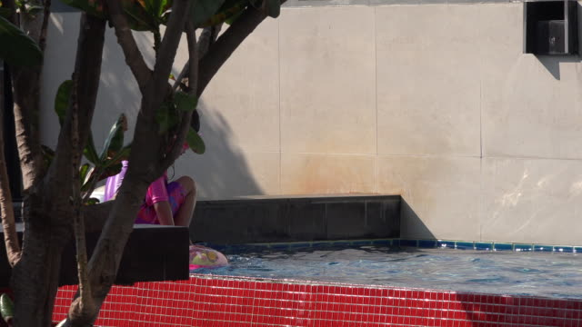 woman is playing in the pool along with her rubber rings. - historical reenactment stock videos & royalty-free footage