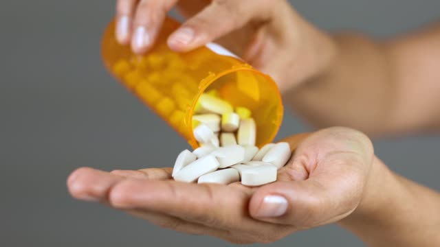 woman is pouring excessive amount of pills on hand - aspirin stock videos & royalty-free footage