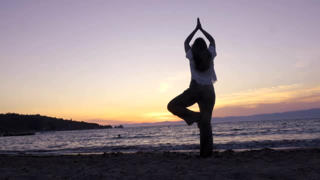 stockvideo's en b-roll-footage met een vrouw is het beoefenen van yoga bij zonsondergang - in kleermakerszit