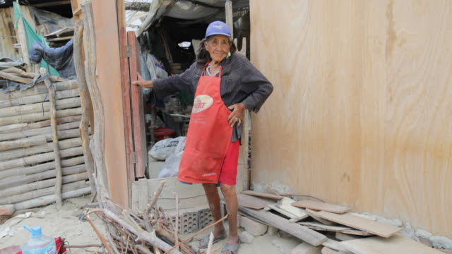 woman is proudly standing in front of a wooden hut. she is wearing a blue baseball cap and a skirt over her dress in a slum in piura, peru. - baseball cap stock videos & royalty-free footage