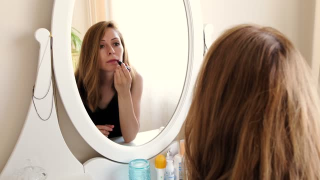 woman is putting on lipstick in front of the mirror. - red lipstick stock videos & royalty-free footage