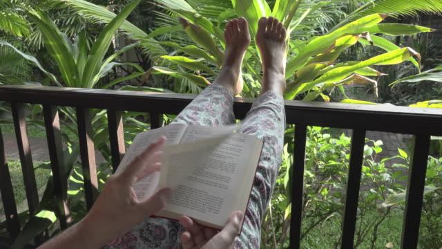 A woman is reading a book on a veranda in a tropical garden