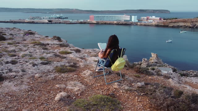 woman is reading a book on cliff with beautiful view - dusk stock videos & royalty-free footage