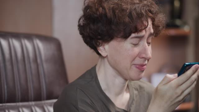 vídeos y material grabado en eventos de stock de la mujer está leyendo su teléfono inteligente y llorando - mujeres de mediana edad