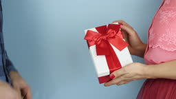 Woman is receiving gift box for St. Valentine's Day or Birthday. Male hands are giving white present box with red ribbon bow to female. Holiday celebration concept
