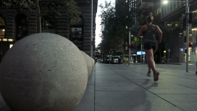 a woman is seen jogging during the morning commute in sydney cbd on march 31 2020 in sydney australia public gatherings are now limited to two people... - monday morning stock videos & royalty-free footage