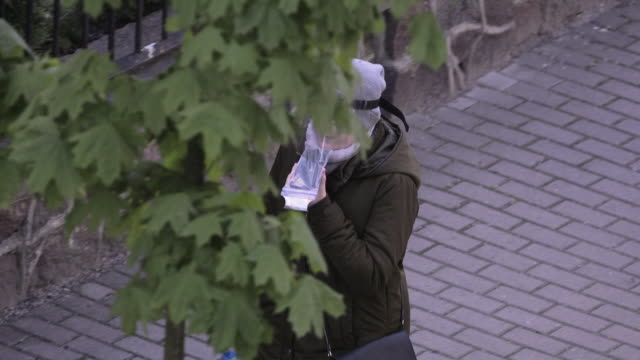 vidéos et rushes de woman is seen on a plastic covered mobile phone while wearing a plastic face mask in warsaw, poland on may 2, 2020. the polish government has... - varsovie
