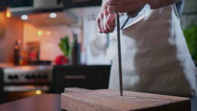 vídeos de stock, filmes e b-roll de mulher está afiando uma faca de chef na cozinha doméstica - afiado