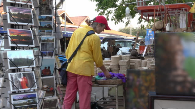 a woman is shopping at old market area in downtown siem reap - お土産点の映像素材/bロール