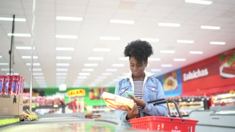 woman is shopping in supermarket and scanning barcode with smartphone - advertisement stock videos & royalty-free footage