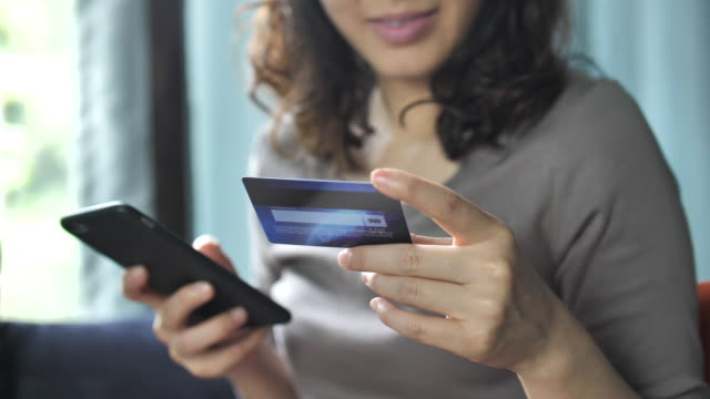 woman is shopping online using a smartphone - acquisto con carta di credito video stock e b–roll