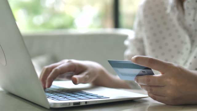 stockvideo's en b-roll-footage met vrouw is winkelen online gebruikt via laptop - werkneemster
