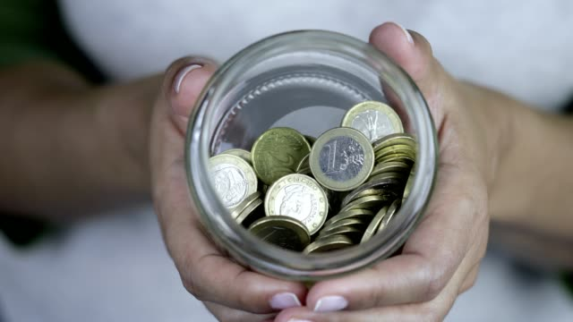 vídeos de stock e filmes b-roll de woman is showing european union money in jar - european union coin