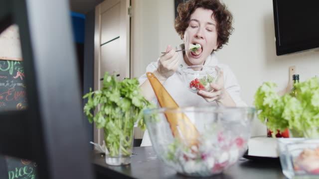 女性はテーブルに座って、自分のために新鮮な野菜サラダを作っています - シェーブルチーズ点の映像素材/bロール