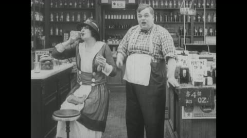 vidéos et rushes de 1917 a woman is so taken by the scent of a fragrance a drug store clerk (fatty arbuckle) sprays that she happily drinks it - sentir